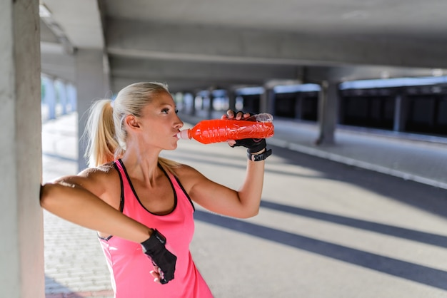 Young woman drinking water after r exercise