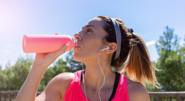 Young woman drinking water after running listening to music with headphones healthy lifestyle