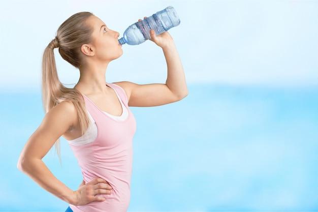 운동 후 물을 마시는 젊은 여자