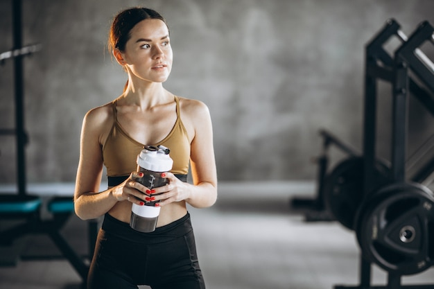 若い女性は、ジムでのエクササイズ後の水を飲む