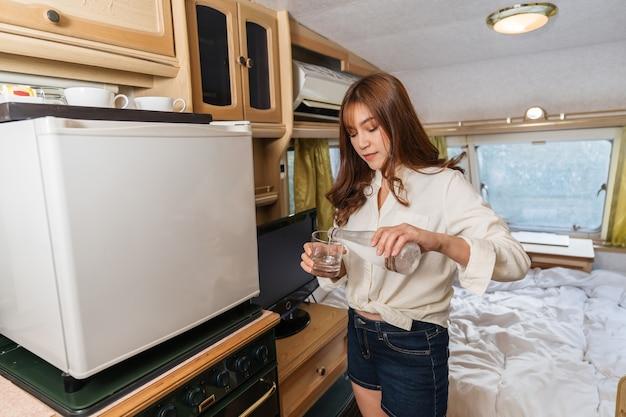 젊은 여성이 마시는 물과 캠핑카 rv 밴 캠핑카에 살고