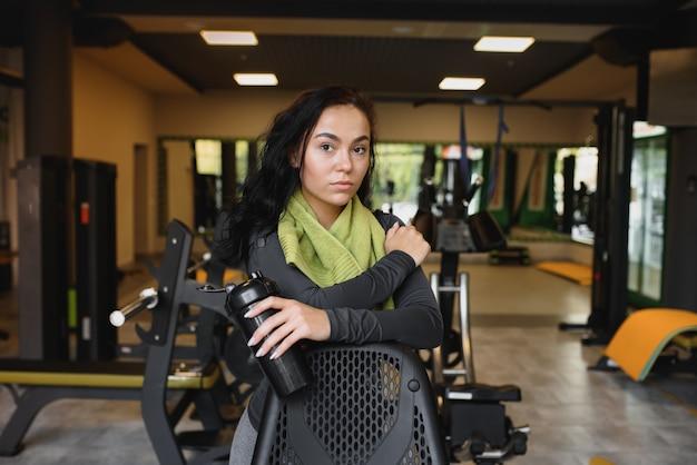 Молодая женщина пьет воду и делает перерыв после тренировки в тренажерном зале
