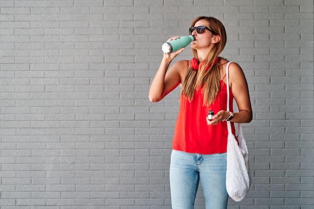 若い女性はボトルから水を飲む。