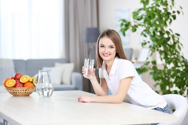 台所でガラスから水を飲む若い女性