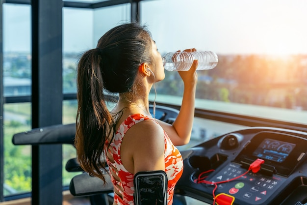 Young woman drinking water in the gym. exercise concept.