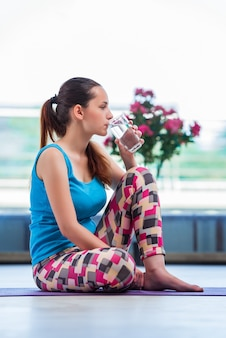 Young woman drinking water in gym health concept