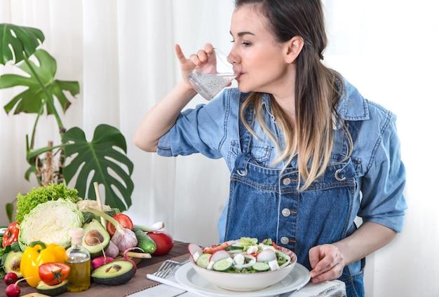 Acqua potabile della giovane donna al tavolo con le verdure