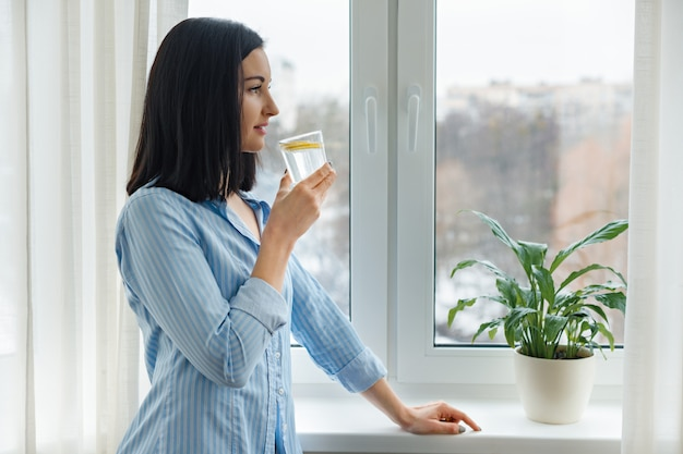 Young woman drinking water with lemon, vitamin drink in winter