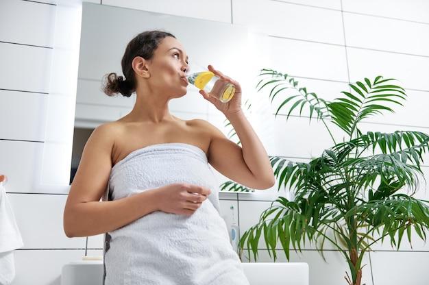 若い女性はレモンとコップ1杯の水を飲みます。ヘルスケア、健康的なライフスタイル、デトックスダイエットの概念。