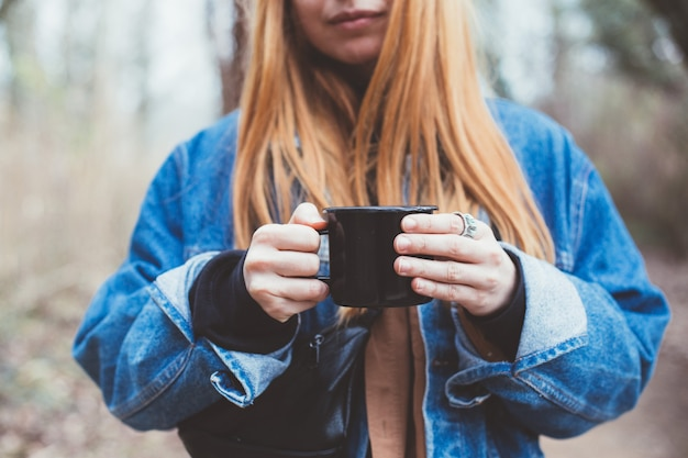 Young woman drinks coffee cup on lake shore