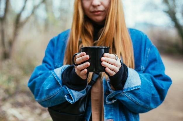 Молодая женщина пьет чашку кофе на берегу озера