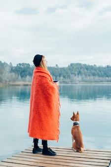 若い女性は湖岸でコーヒーカップを飲みます