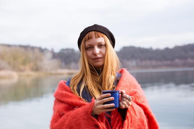 호숫가에 젊은 여자 음료 커피 컵