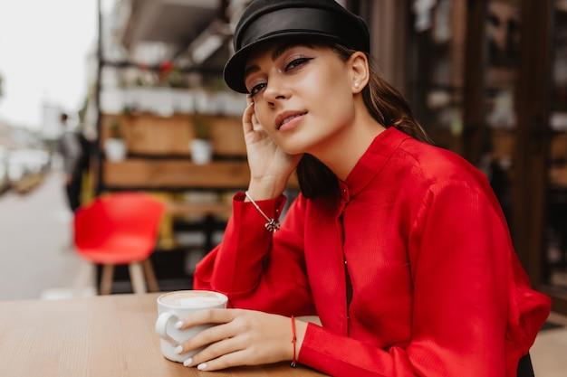 젊은 여자는 거리 카페에서 커피를 마신다. 비싼 블라우스에 아름다운 화장을 한 여자는 신비하게