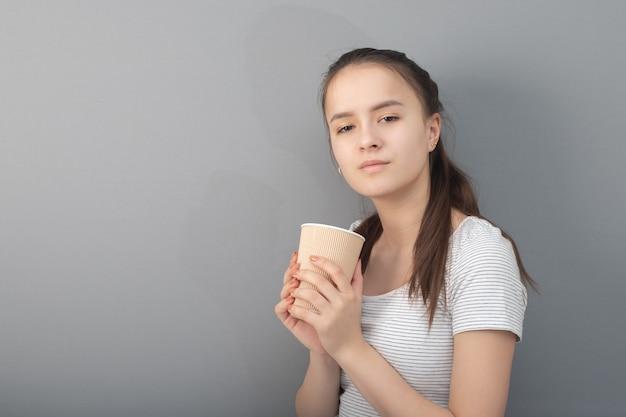 젊은 여자는 회색 배경에 커피를 마신다
