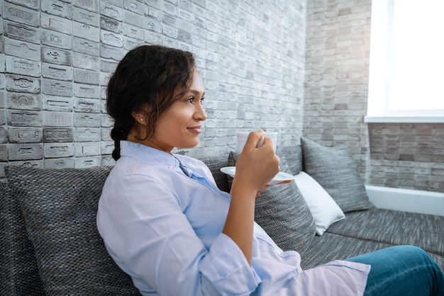 The young woman drinks coffee while sitting on the sofa near the window.