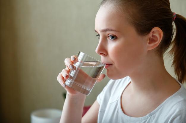 若い女性は、朝起きた後、1 杯の純水を飲みます。幸せな 10 代の少女は、透明なカップのきれいな水を飲むことで、体の健康のための水のバランスを維持します。