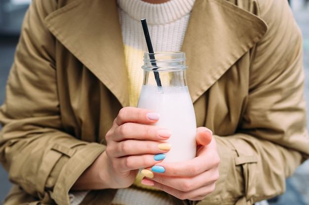 A young woman drinks a milkshake outdoors from a stylish glass jar with a straw