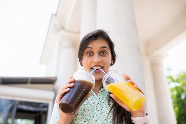 Young woman drinks two cocktails with ice in plastic cups with straw