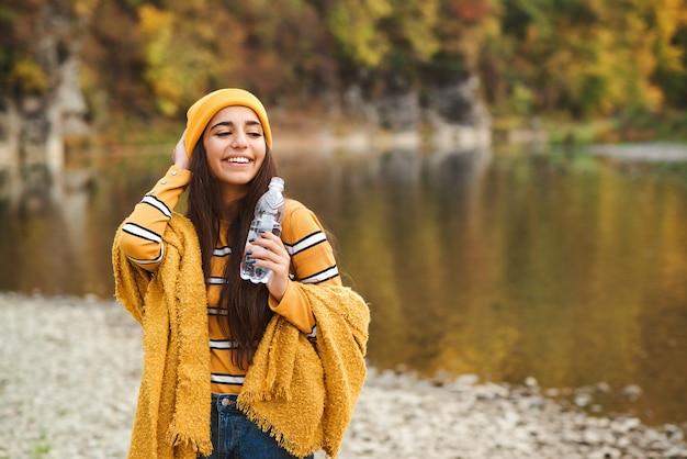 Молодая женщина пьет воду на природе. красивая женщина, идущая в осеннем парке. девушка наслаждается осенней погодой.