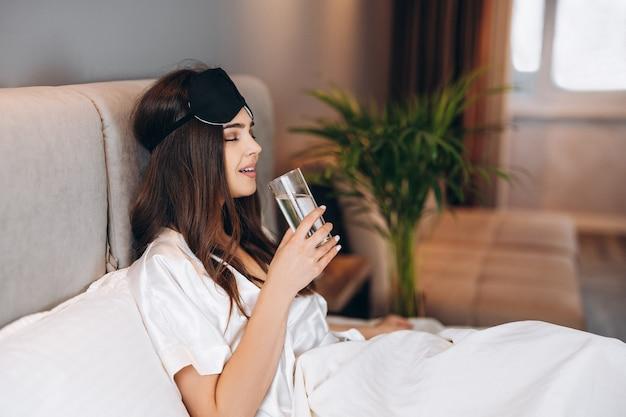 若い女性はベッドで水を飲みます。寝室のベッドに水を一杯入れた茶色の髪のモデル。朝または就寝前にコップ一杯の水を飲む。飲料水を楽しんでいる若い女性。
