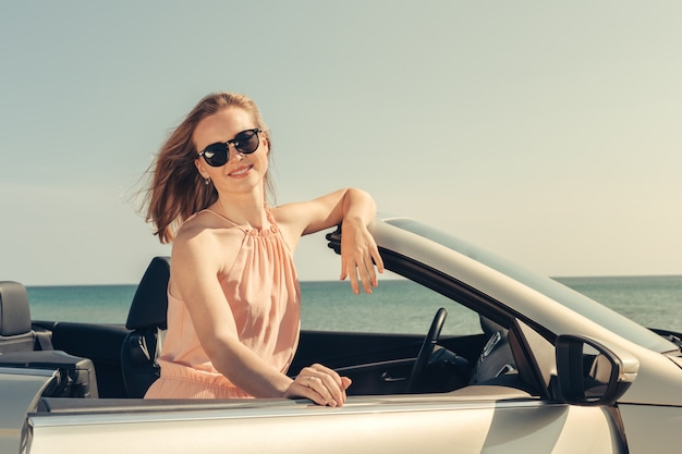 Young woman drive a car on the beach