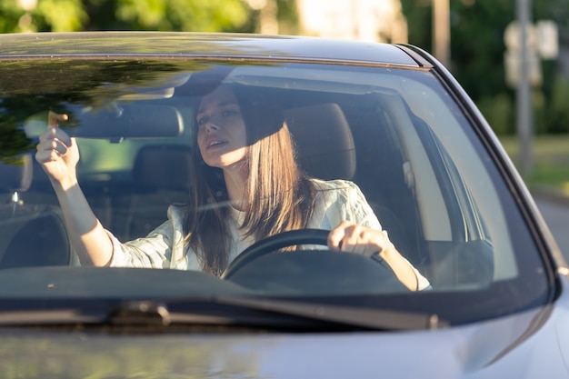 Young woman driver adjust mirror of back rear view inside car before driving holding steering wheel