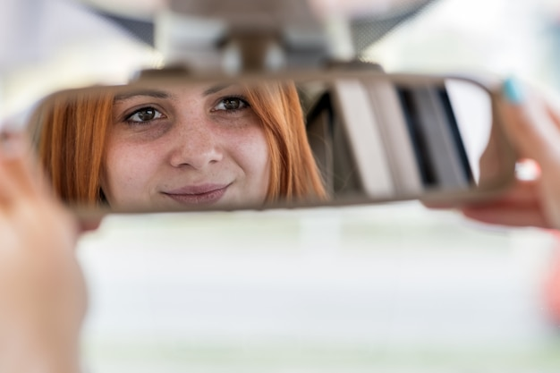 Young woman driver checking rearview mirror while driving a car