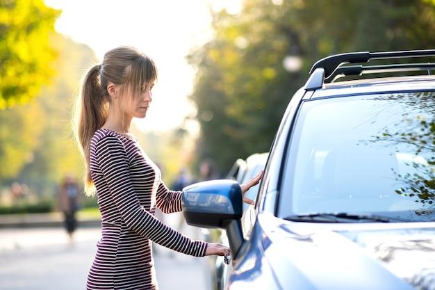 Водитель молодой женщины, наслаждаясь теплым летним днем, стоя рядом с ее автомобилем на улице города. концепция путешествий и отдыха.
