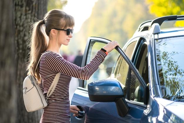 도시 거리에서 그녀의 차 옆에 서서 따뜻한 여름날을 즐기는 젊은 여성 운전사. 여행 및 휴가 개념입니다.