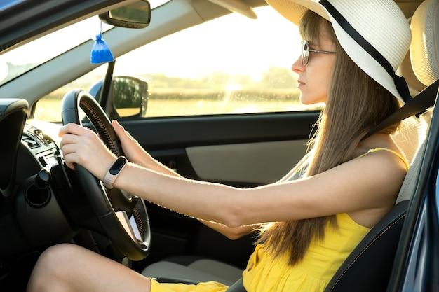 여름 노란 드레스와 밀 짚 모자 차를 운전 하는 젊은 여자 드라이버.
