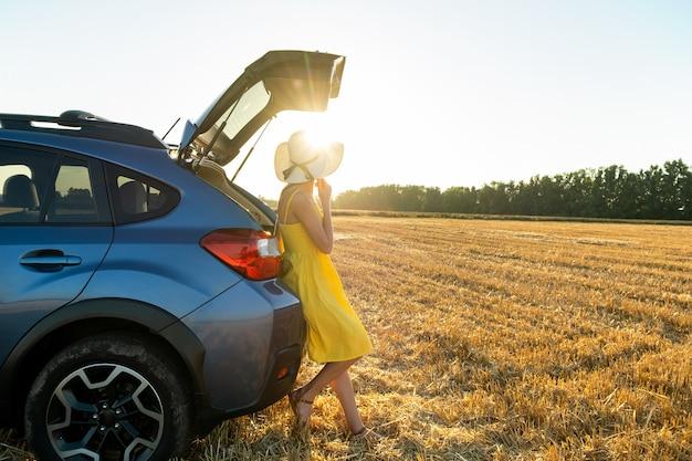 Водитель молодой женщины в желтом платье лета и соломенной шляпе стоя около ее автомобиля наслаждаясь теплым летним днем на заходе солнца.