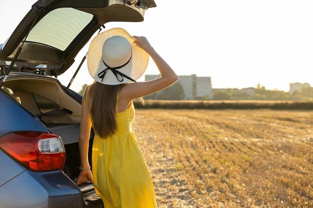 Водитель молодой женщины в желтом летнем платье и соломенной шляпе, стоя возле своей машины, наслаждаясь теплым летним днем на закате.