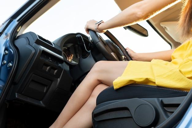 운전대 뒤에 노란색 여름 드레스를 입은 젊은 여성 드라이버 다리.
