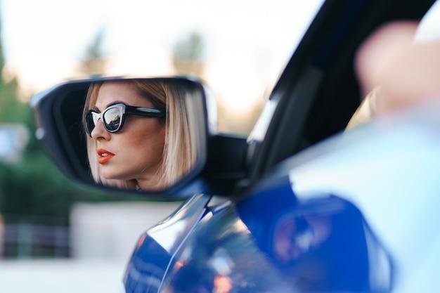 若い女性ドライバーが車のサイドミラーを見て、曲がる前にラインが空いていることを確認します。