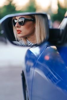 Молодая женщина-водитель смотрит в зеркало бокового вида автомобиля, перед поворотом проверяет, свободна ли линия.