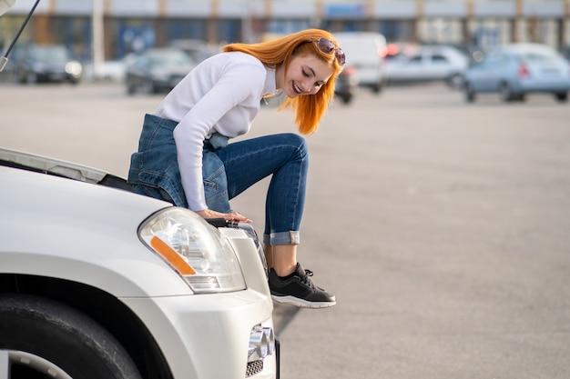Водитель молодой женщины около сломанной машины с вытолкнутым капюшоном в ожидании помощи