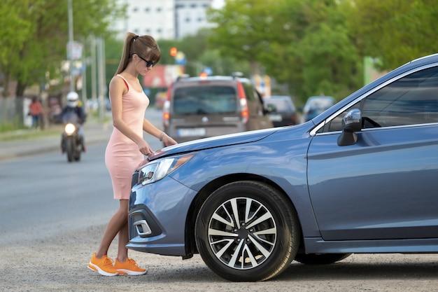 Молодая женщина-водитель, открывая капот автомобиля, осматривает сломанный двигатель на городской улице. концепция неисправности автомобиля.
