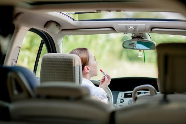 若い女性ドライバーの赤い髪の10代の少女は、車の運転中にメイクアップを適用して唇を描いています。