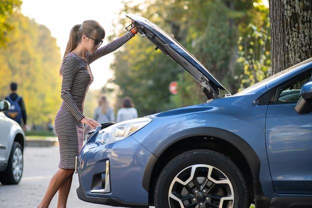 Молодая женщина-водитель, стоящая возле сломанной машины с открытым капотом, имеет проблемы с ее транспортным средством.