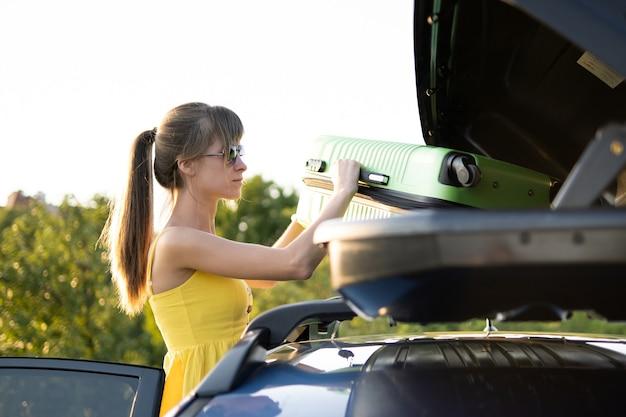 車のルーフラックから緑のスーツケースを取る若い女性ドライバー。旅行と休暇のコンセプト。