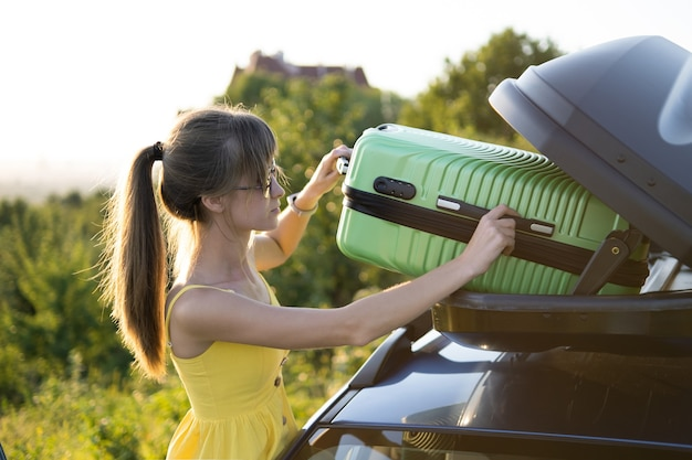 Young woman driver taking green suitcase from car roof rack. travel and vacations concept.