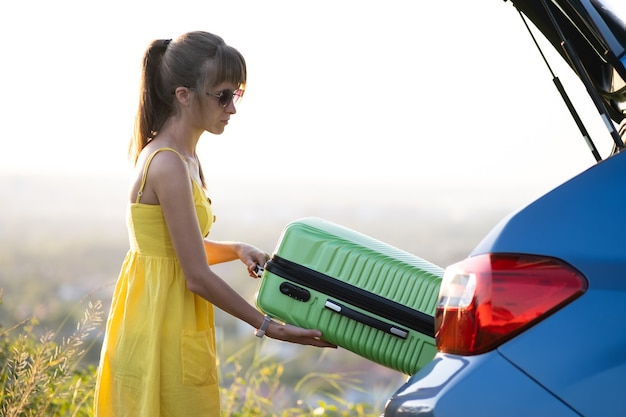 Young woman driver taking green suitcase out from car trunk. travel and vacations concept.