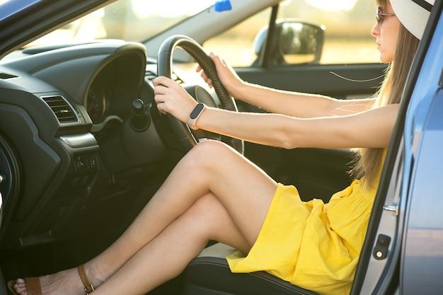 노란 드레스와 밀짚모자를 쓴 젊은 여성 운전자는 차를 운전하는 운전대 뒤에 앉아 있습니다. 여름 휴가 및 여행 개념입니다.