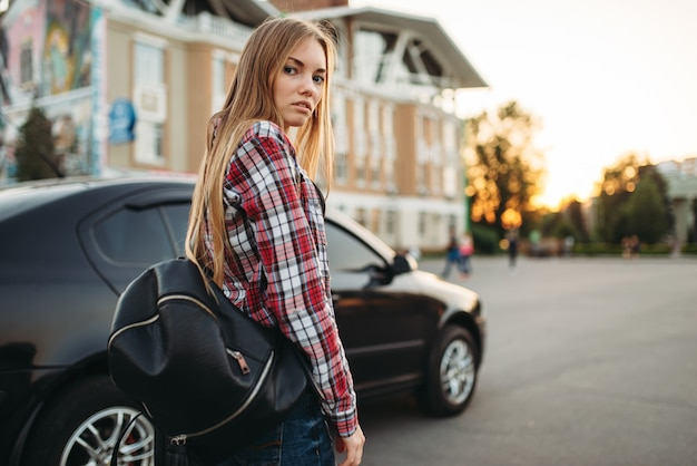 Young woman driver with bag against a car