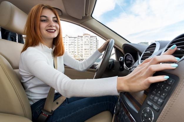 車を運転し、ヒーターを調整する若い女性