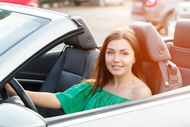 Молодая женщина за рулем автомобиля в городе.