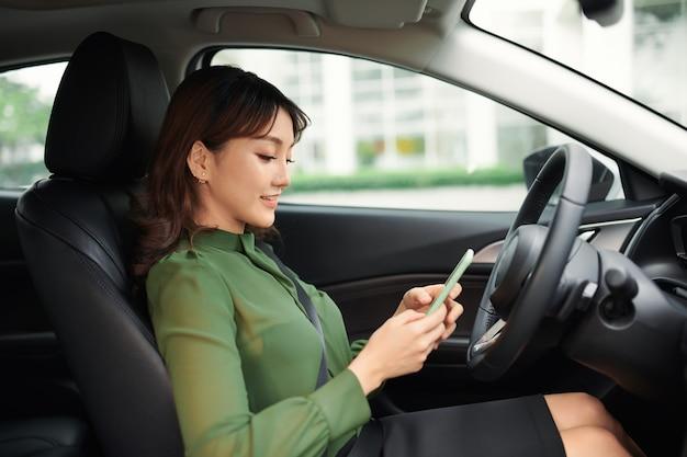 전화 화면을보고 차를 운전하는 젊은 여자
