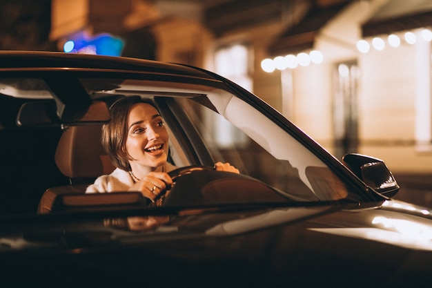 Young woman driving in car at night