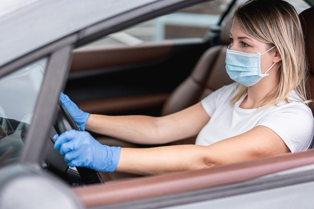 Young woman driving car while wearing safety face mask
